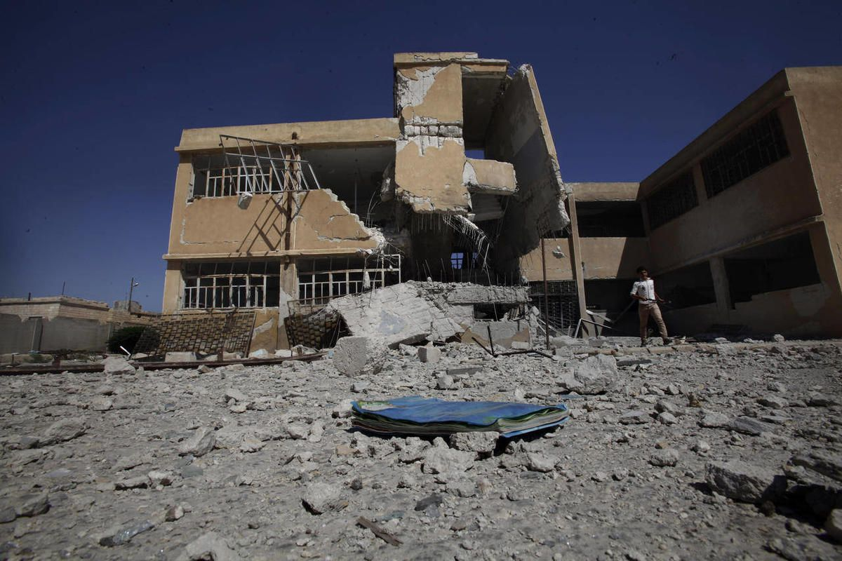 A book is left on the ground at the yard of a school destroyed in government airstrike in Tel Rifaat, on the outskirts of Aleppo, Syria, Sunday, Sept. 16, 2012.  A new school year began in Syria on Sunday, but the country's agonizing civil war is keeping