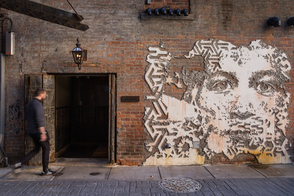 The side of a red brick building in Belt Alley in Detroit. There is a metal mosaic of a man on the building.