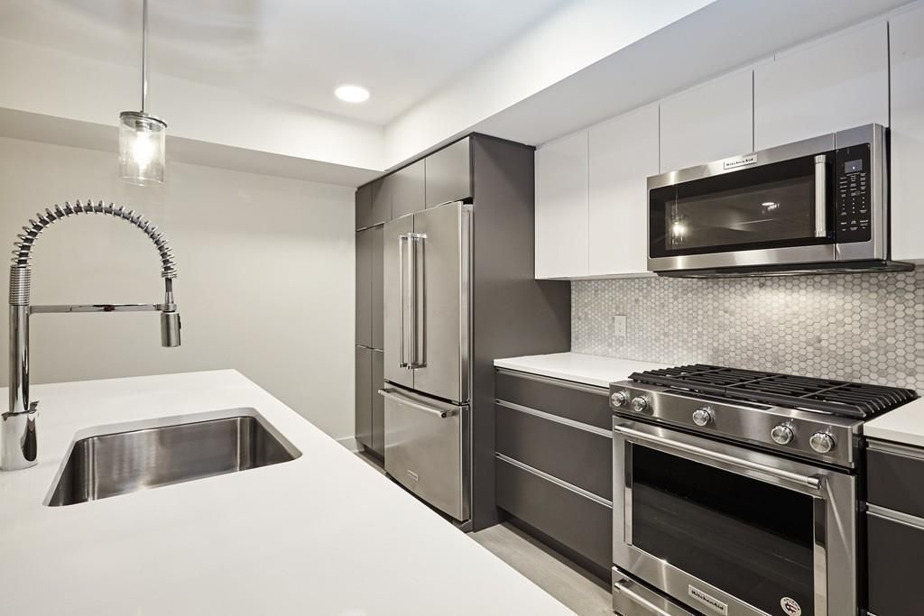 A modern kitchen with a large granite island and a double-door fridge.