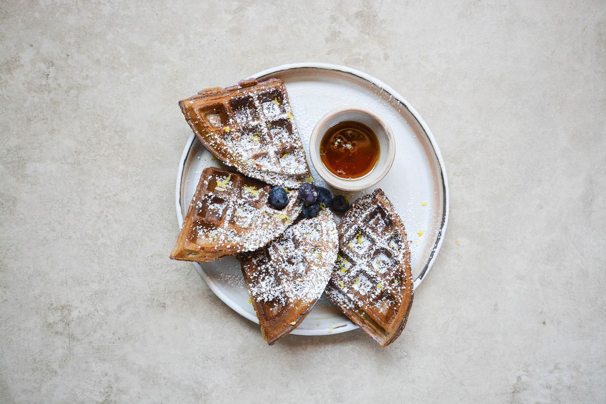Four triangles of a browned waffle on a plate, with syrup.