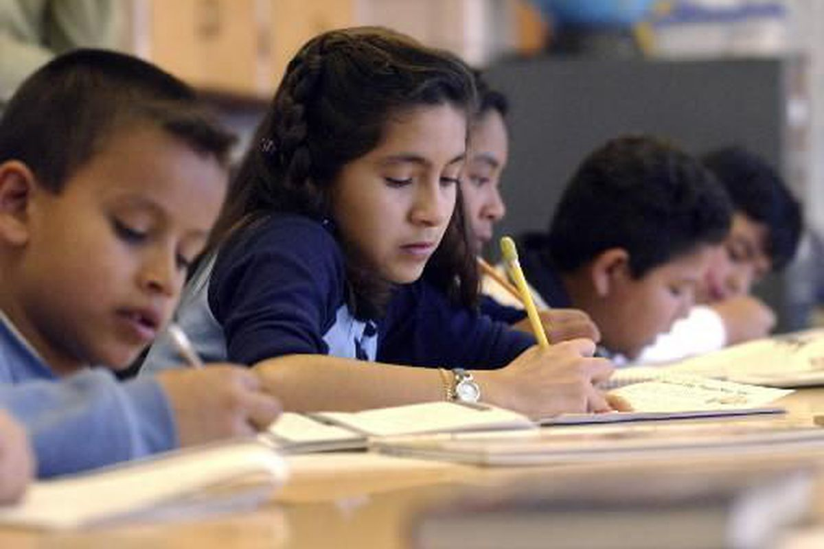 Students sit in line at a table and fill out practice for a standardized test.