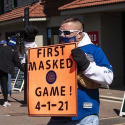 """Greg Cooper, 58, of Springfield, holds a sign that says """"First masked game 4-1-21"""" outside Wrigley Field on Opening Day."""