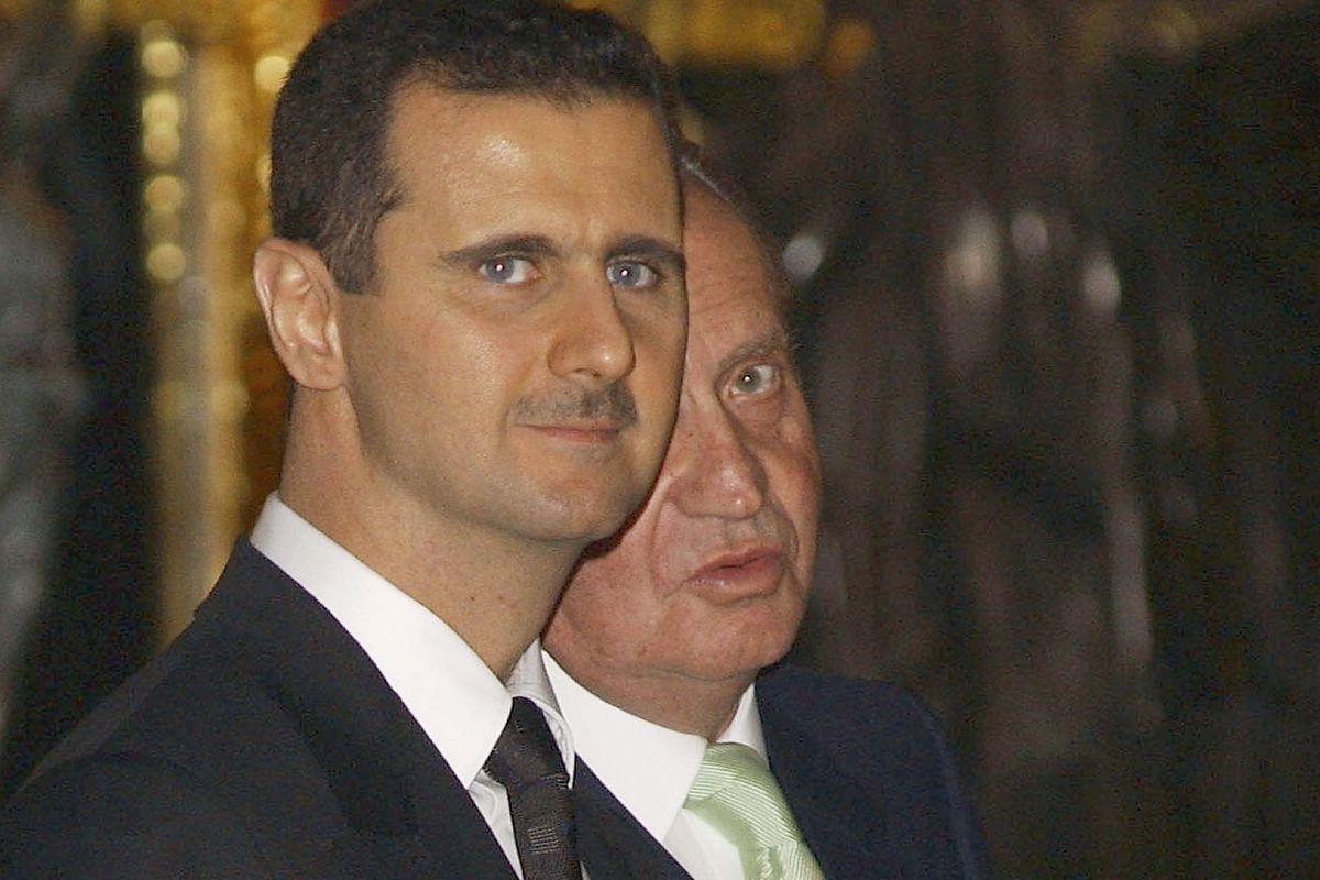Assad (L) with King Carlos II of Spain in 2004.