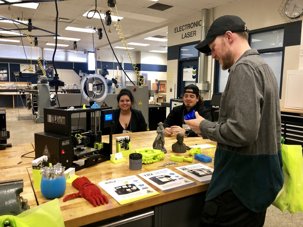 Staff at the Advanced Manufacturing Academy of the St. Vrain School District work with a 3D printer during an open house on Thursday.