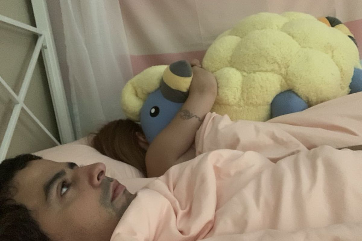 A man in bed with his girlfriend, who is hugging an enormous plushie.