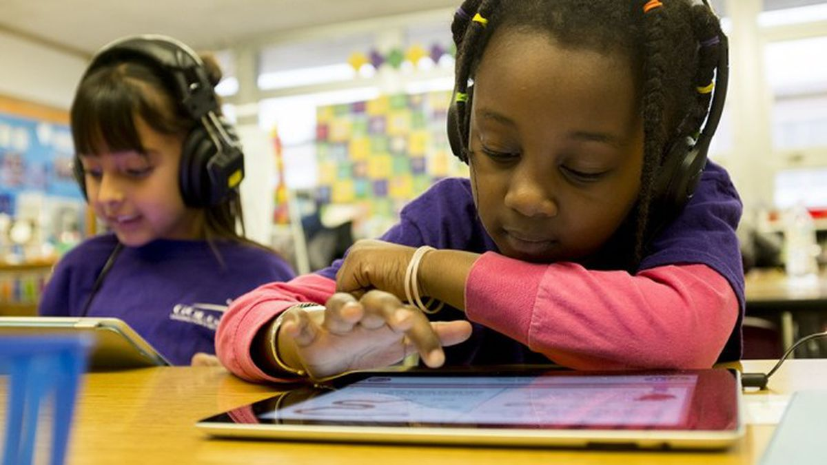 A young student works on an iPad.