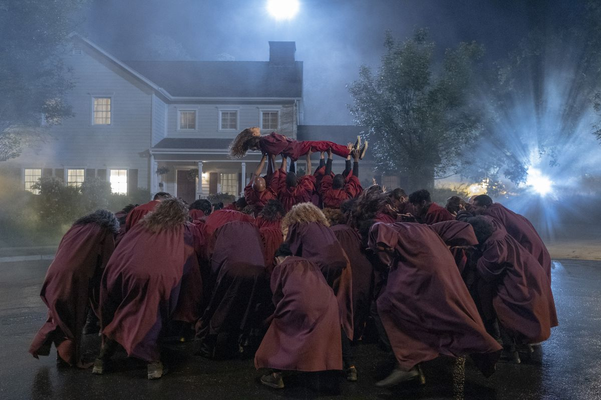 A crowd of people in red robes huddle together, elevating a girl in red sweats and dark hair — Zendaya, as Rue — into the sky. Their bodies all point towards the center of the huddle.