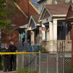 Cleveland Police stand outside a home where they say missing women, Amanda Berry, Gina DeJesus and Michele Knight were found in the 2200 block of Seymour Avenue in Cleveland on Monday, May 6, 2013. The three women who went missing about a decade ago were found alive in a residential area just south of downtown, and a man was arrested. (AP Photo/Plain Dealer, Scott Shaw) MANADATORY CREDIT CLEVELAND PLAIN DEALER