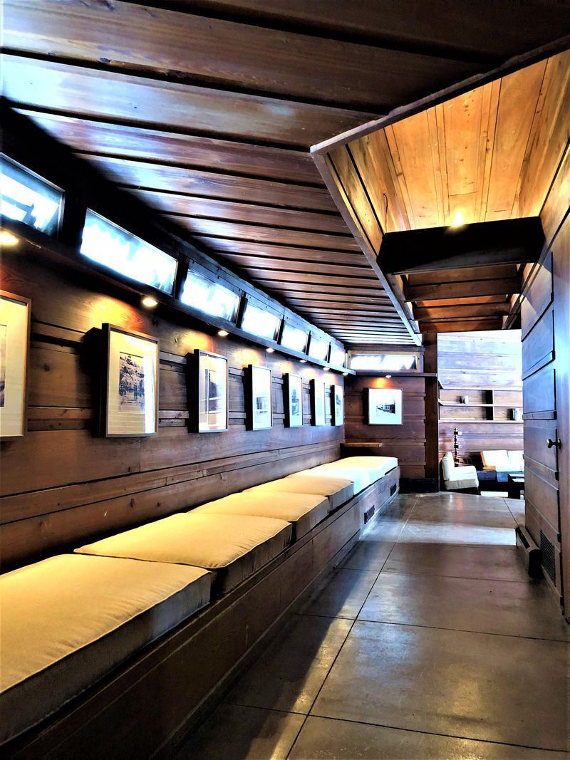 A long hallway has a storage bench with cushions on top and historic photos on the walls.