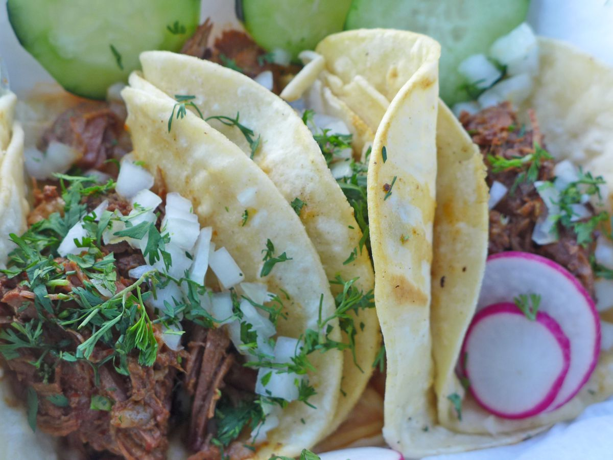 Three tacos overstuffed with dark meat topped with chopped onions and cilantro.