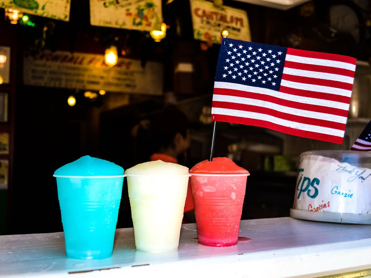 blue, red, and lemon Italian ices in plastic cups on a counter with an American flag.