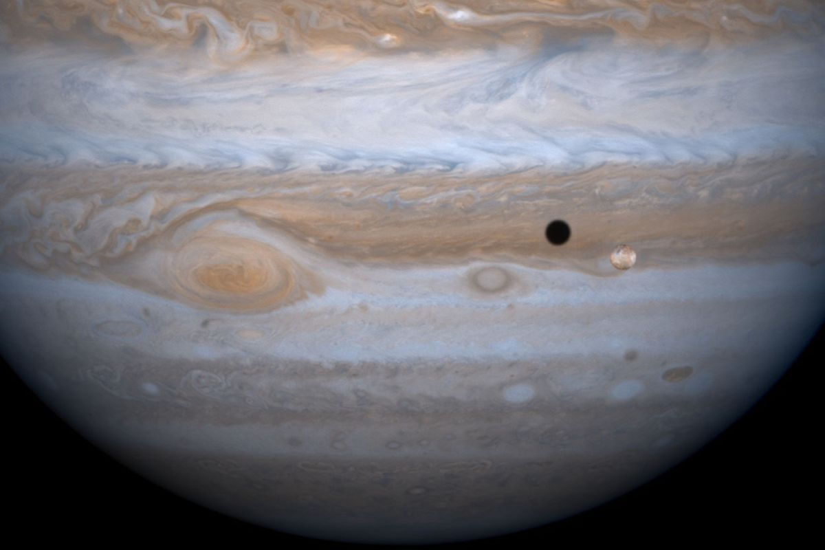A massive orb, covered in gray, brown, red, and blue whirls that look like dyed gusts of wind hovers behind a little circle of brown that casts a small shadow on the planet behind it.