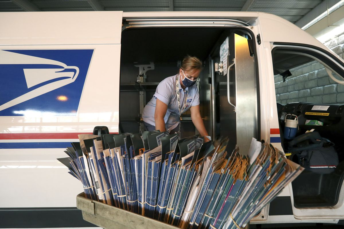 U.S. Postal Service letter carrier Heidi Barlow organizes mail that she will deliver from the post office in the Sugar House neighborhood of Salt Lake City on Wednesday, Oct. 7, 2020.