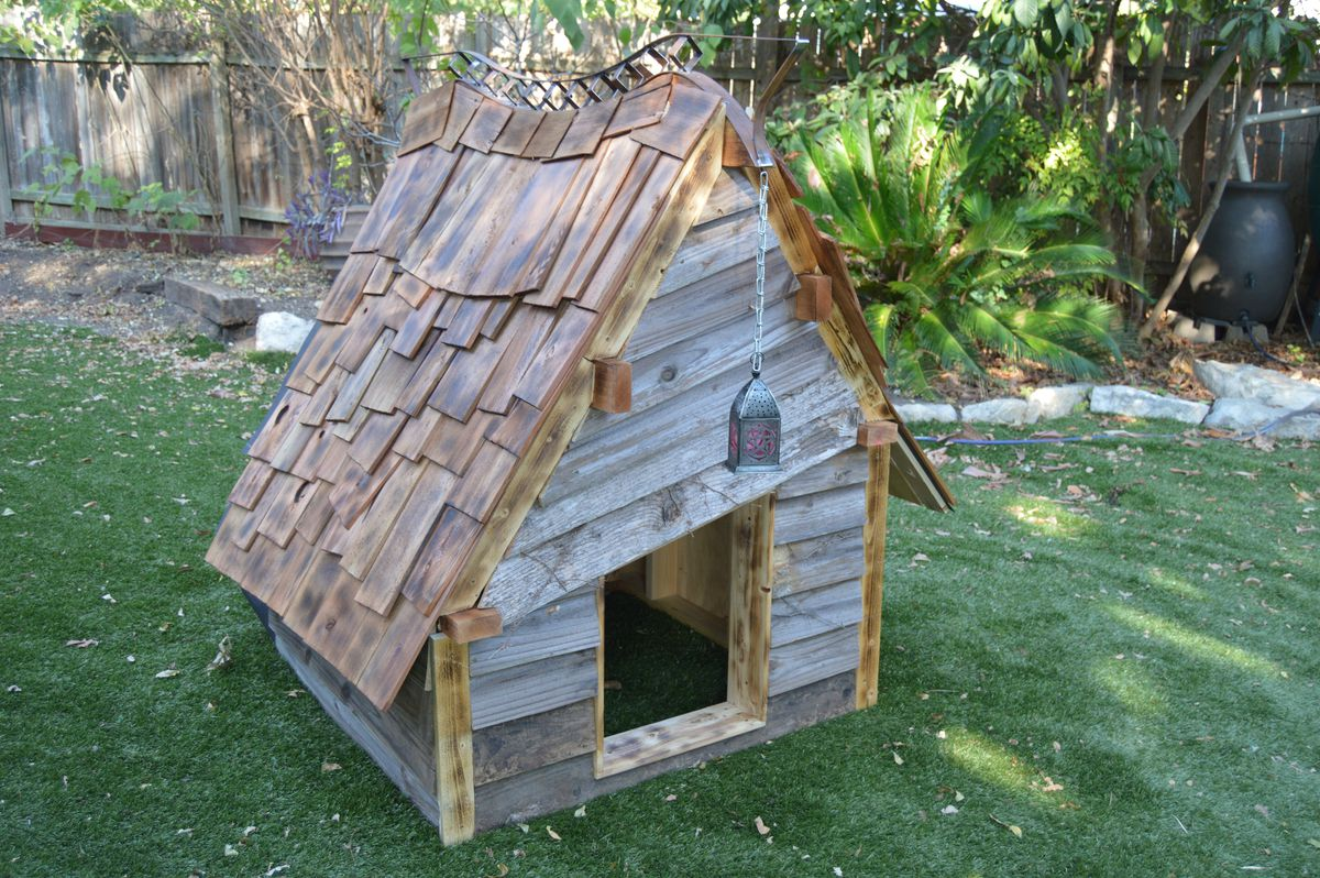 Rustic cabin-style dog house with a shinkgled peaked roof and weathered wood siding.