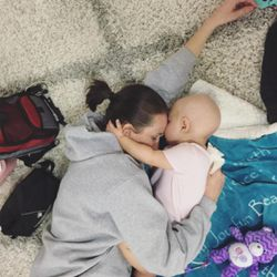 Mother and daughter, Lindsey and Harper, share a tender moment before 1-year-old Harper heads back to the hospital for more cancer treatment.