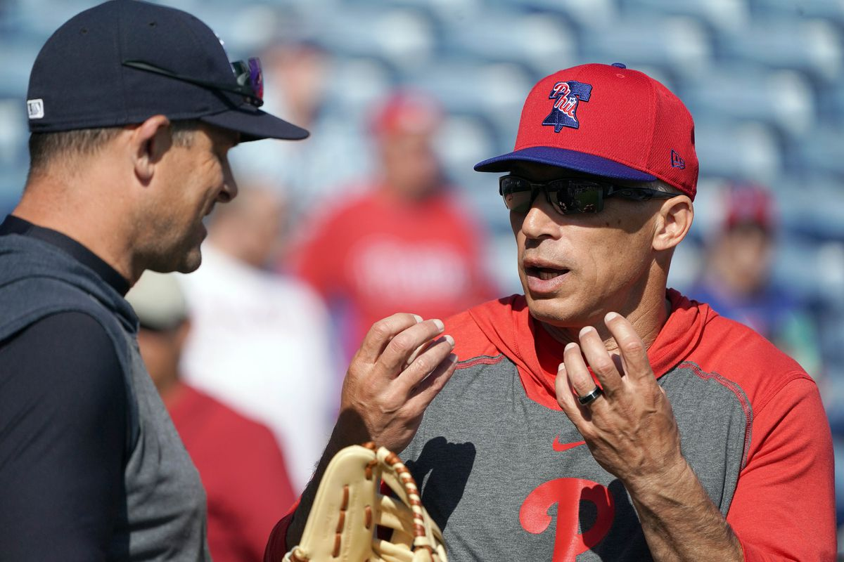 New York Yankees manager Aaron Boone (17) and Philadelphia Phillies manager Joe Girardi (25) talk during batting practice before their game at Spectrum Field.