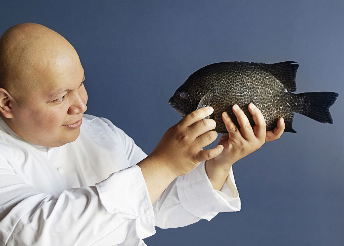 The chef Mark Garcia dressed in a white chef's coat stands against a blue background holding a black fish in his hands