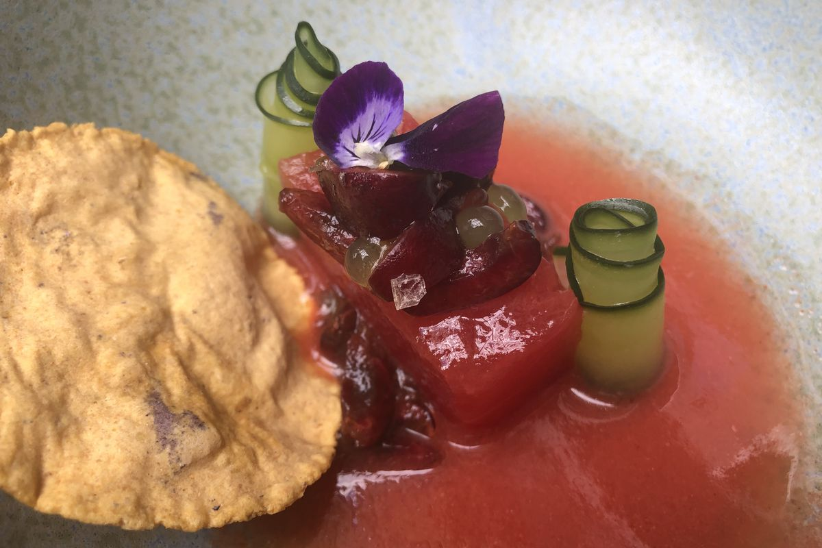 A square of watermelon comes topped with edible flowers, cucumber roses, and a masa tostada, plated in a pool of chile-scented tomato juice. The dish is one of Lauro Romero's dishes at República.