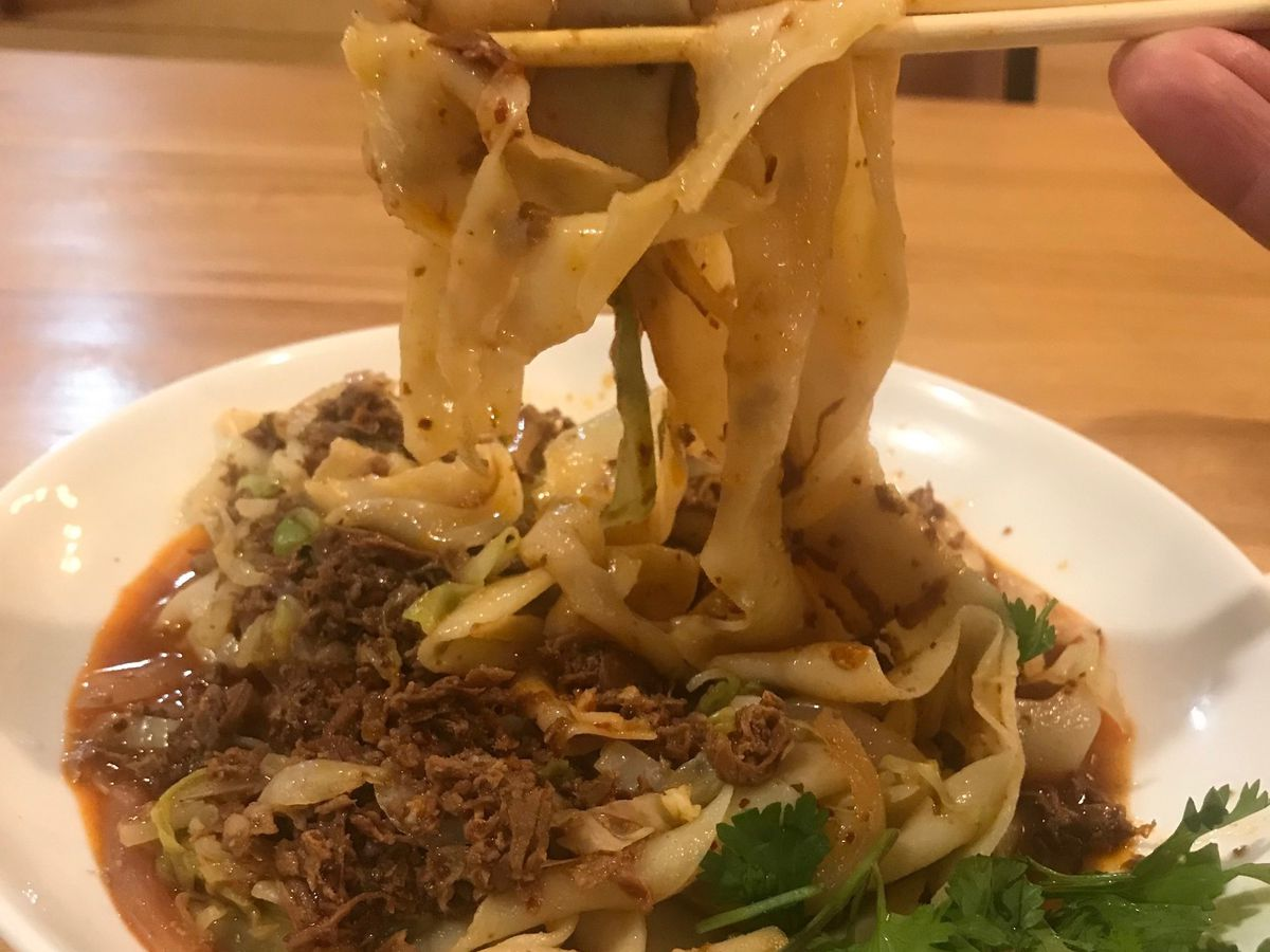 A closeup view of a bowl filled with lamb cumin noodles and herbs, pulled with chopsticks.