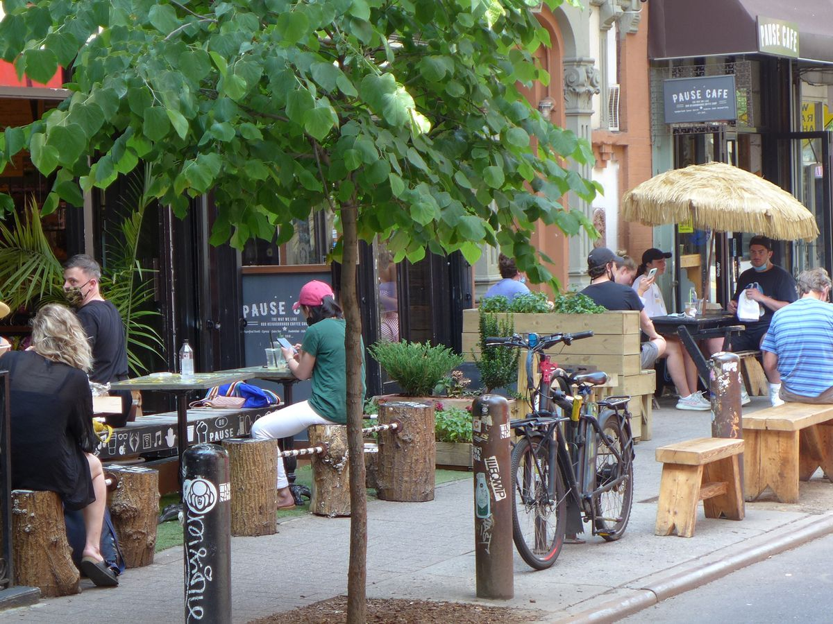 A jumble of tables on the sidewalk with a prominent tree.