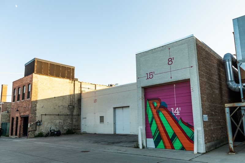 """A row of old warehouse buildings stand jagged together. The closest brick building with a metal rolldown garage door has a red and green graffiti """"R"""" against a pink background."""
