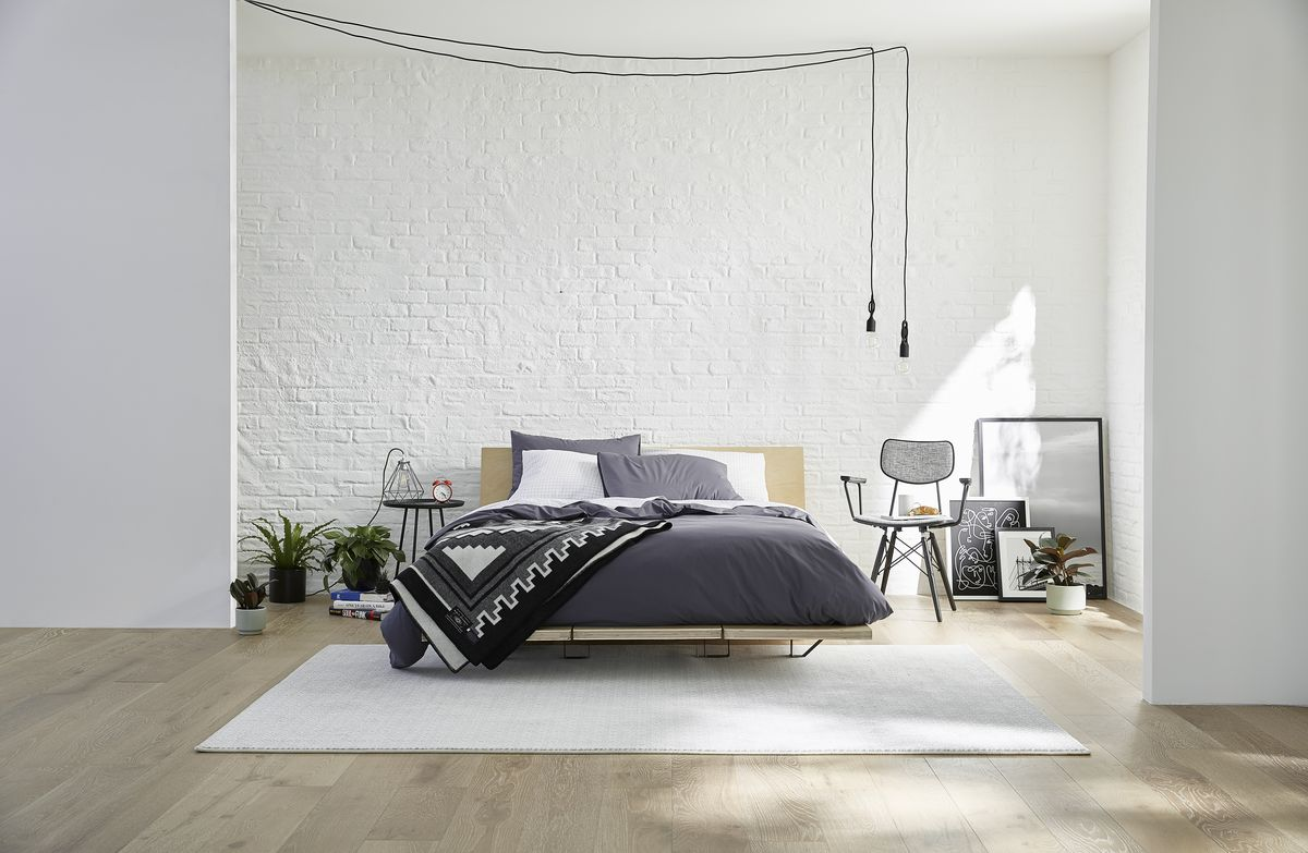 Bedroom with white rug, and bed with gray bedding.