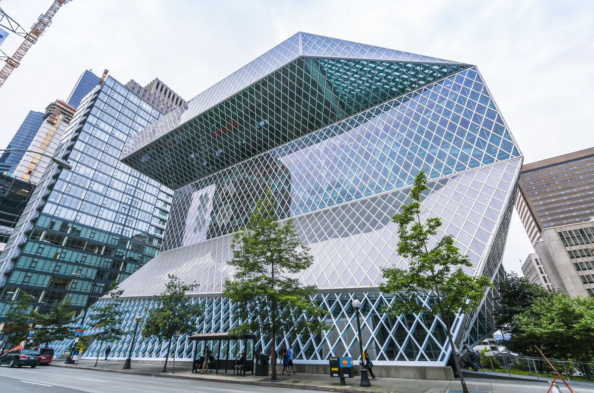 The exterior of the Seattle Public Library. The steel and glass facade is shaped like a diamond and has many windows.