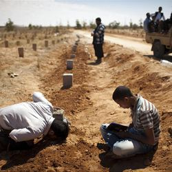 A man kisses the tomb of Hussein Saad Al Awami, a rebel fighter who was killed Monday during fighting against Moammar Gadhafi troops, following his funeral in Benghazi, Libya, Tuesday, May 10, 2011.  (AP Photo/Rodrigo Abd)