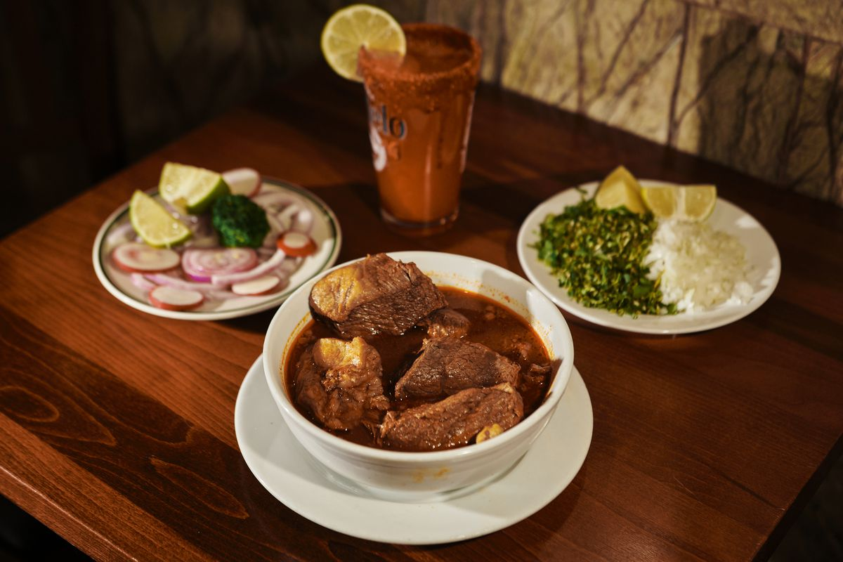 Chunks of stewed beef sit in a bowl of red broth, next to plates of cilantro, onion, lime, radish, and a michelada