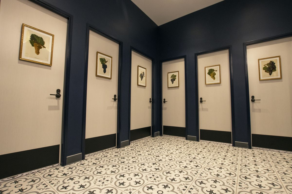 A row of bathroom stalls in a unisex facility with white and black tiling on the floor.