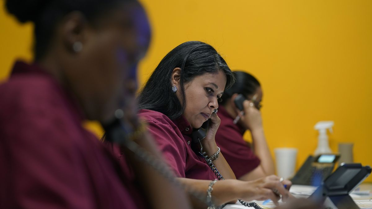 Three women wearing dark red shirts work on the phone in a call center. The woman in the center is the focal point, who appears to be typing as she is on the telephone.
