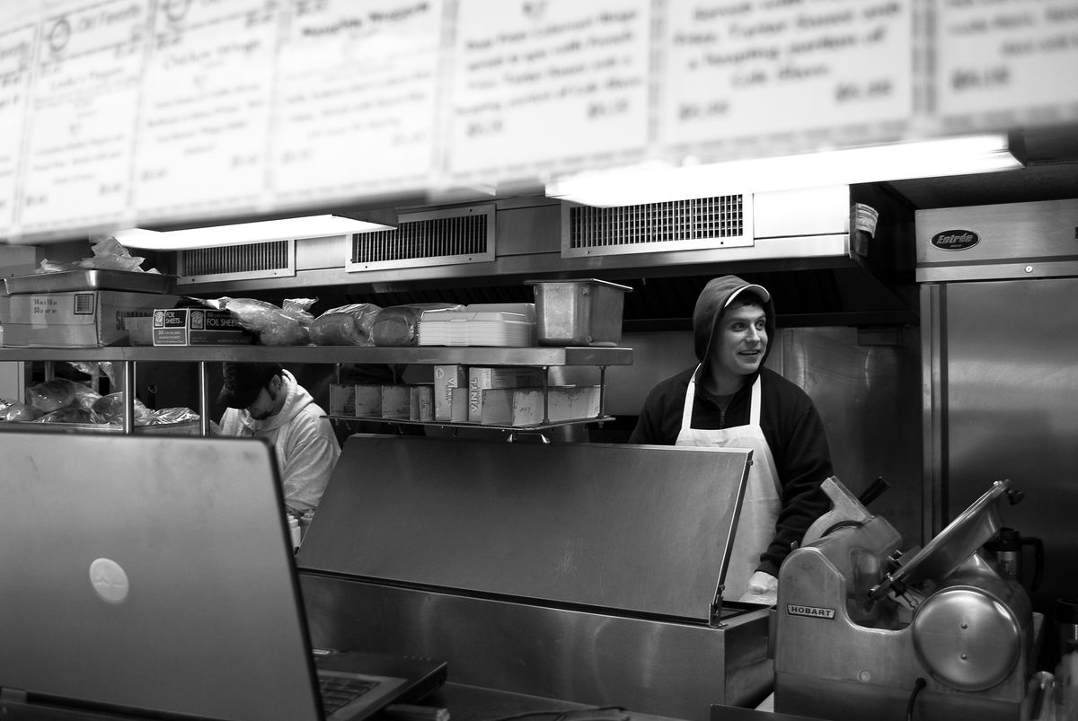 A black and white photograph of a young man working behind the counter at a casual restaurant