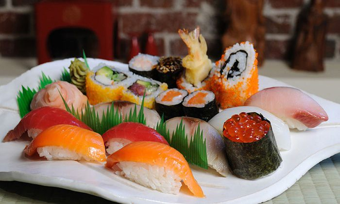 A variety of sushi and sushi rolls on a white plate.