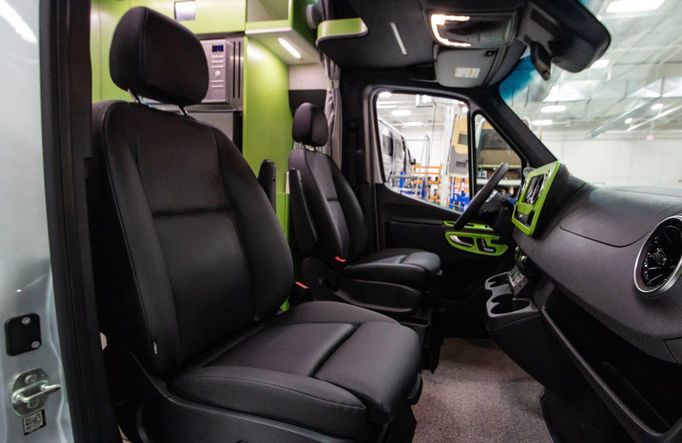 The upper cabin of the camper van features two black cabin seats, a large front window, and a black and green front console.