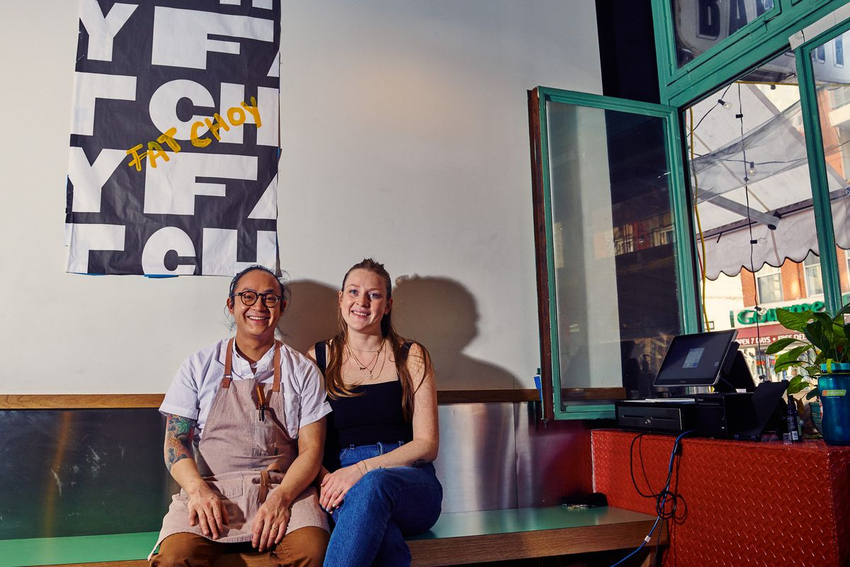 Justin Lee and Katie Lee sit on a bench inside Fat Choy near an open window