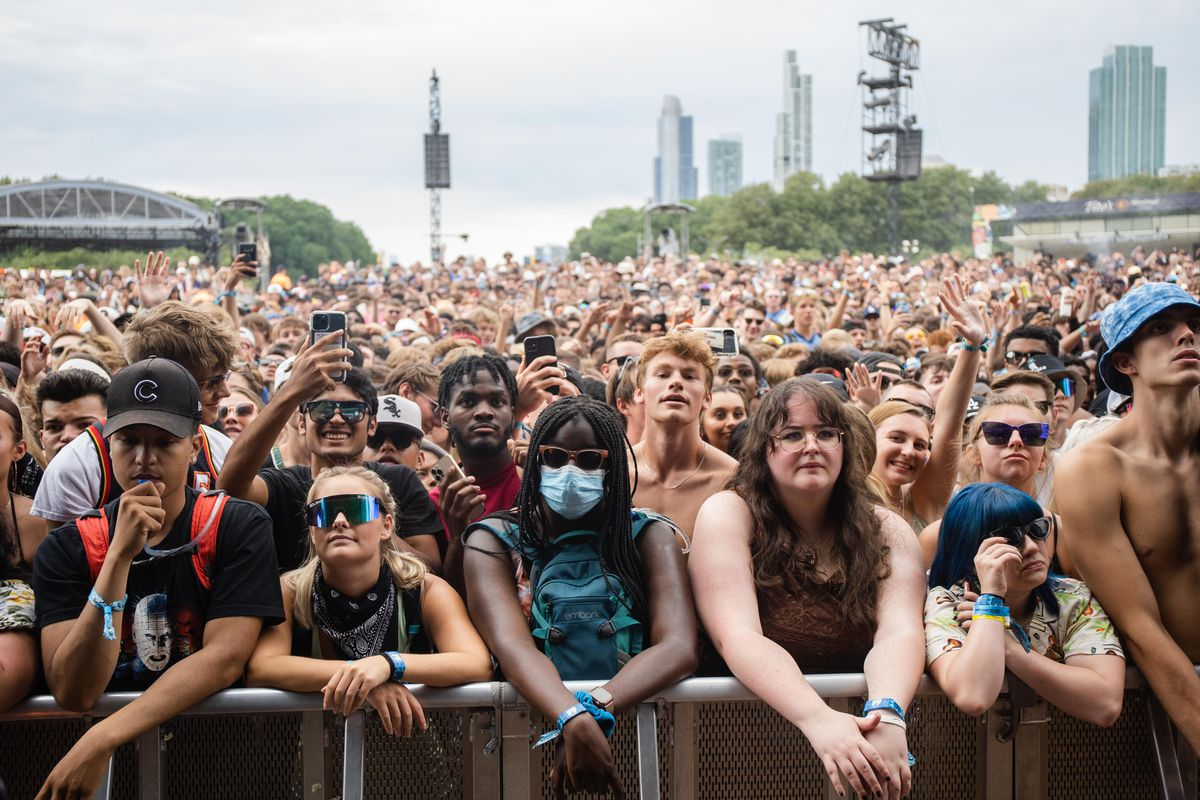 A masked festival goer stands among thousands of unmasked people during Mick Jenkins' show on the second day of Lollapalooza.