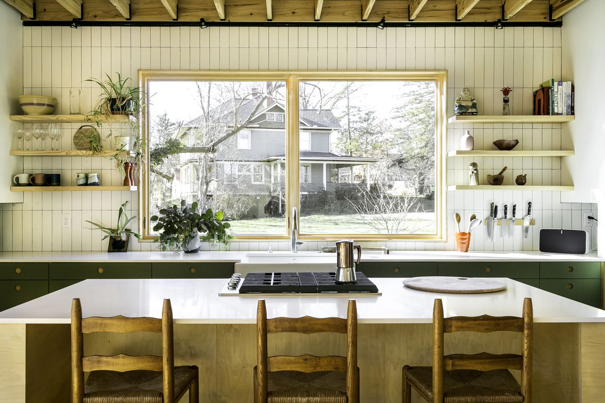 A large wood kitchen island fills the space of the kitchen, which has one large window that overlooks a neighbor's house. The kitchen has green cabinets, white tile, and three wooden stools next to the island.