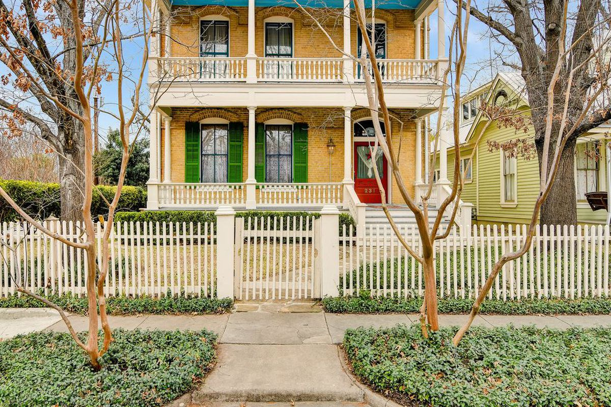 Exterior of pale-brick Victorian style home with off-white front porch and second-floor balcony, bright red front door, and green shutters, with fence in front of yard in the same color as the balcony.