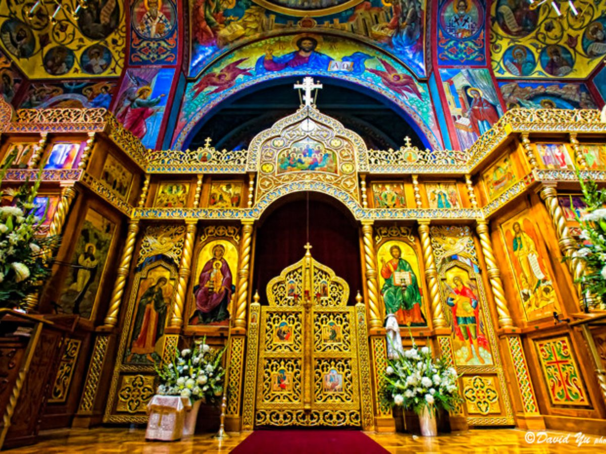 The interior of the Holy Virgin Cathedral in San Francisco. The walls are decorated with colorful inlaid design. The altar has multiple planters with flowers.