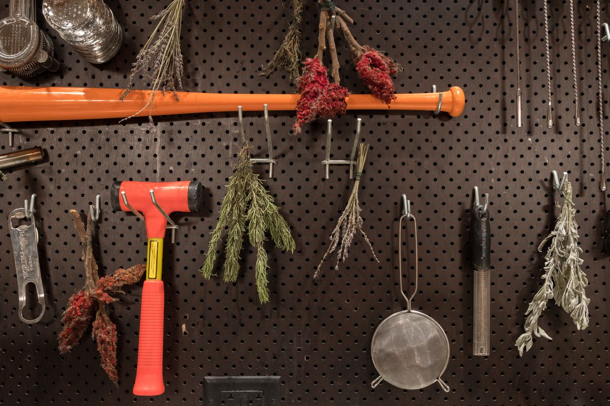 A black peg board with hooks and bar tools