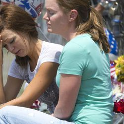 Juliann Ashcraft, left, of Prescott, the wife of Andrew Ashcraft, who was killed battling the Yarnell Hill Fire reacts as she sits by a memorial for the fallen firefighters in front of Prescott Fire Station #7 on Monday, July 1, 2013. Nineteen firefighters have died in the Yarnell Hill Fire that has ripped through half of the town and sent residents to Prescott for safety. (AP Photo/The Arizona Republic, David Wallace)