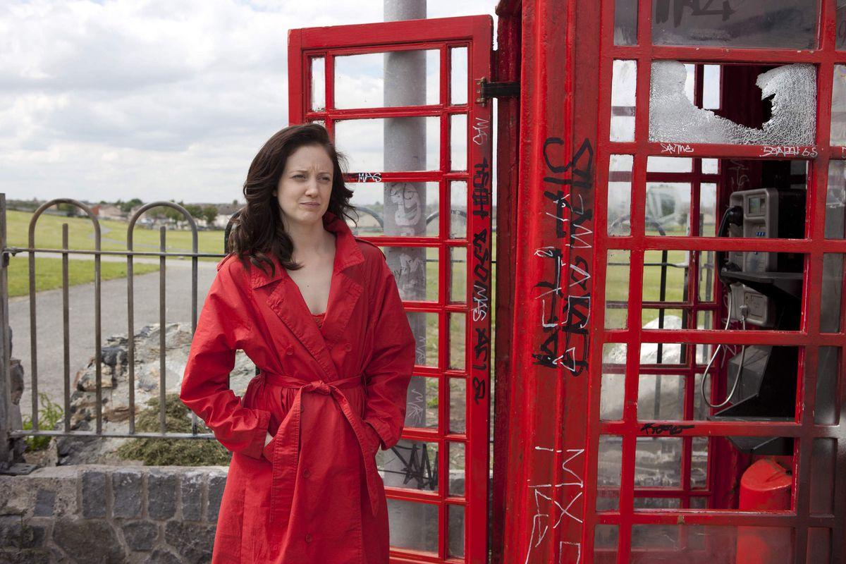Colette (Riseborough), in a red trench coat, stands by a phone booth.