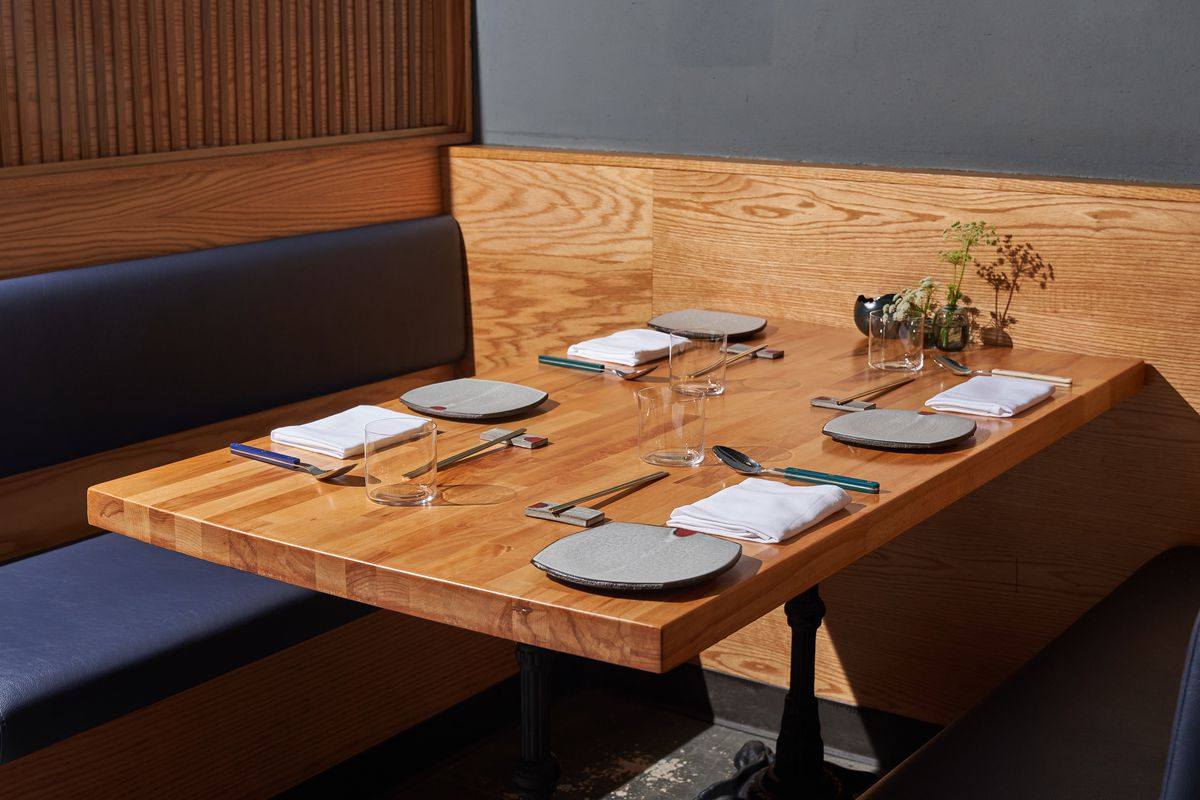 Plates and utensils are set for service at a light wood dining room inside of a restaurant