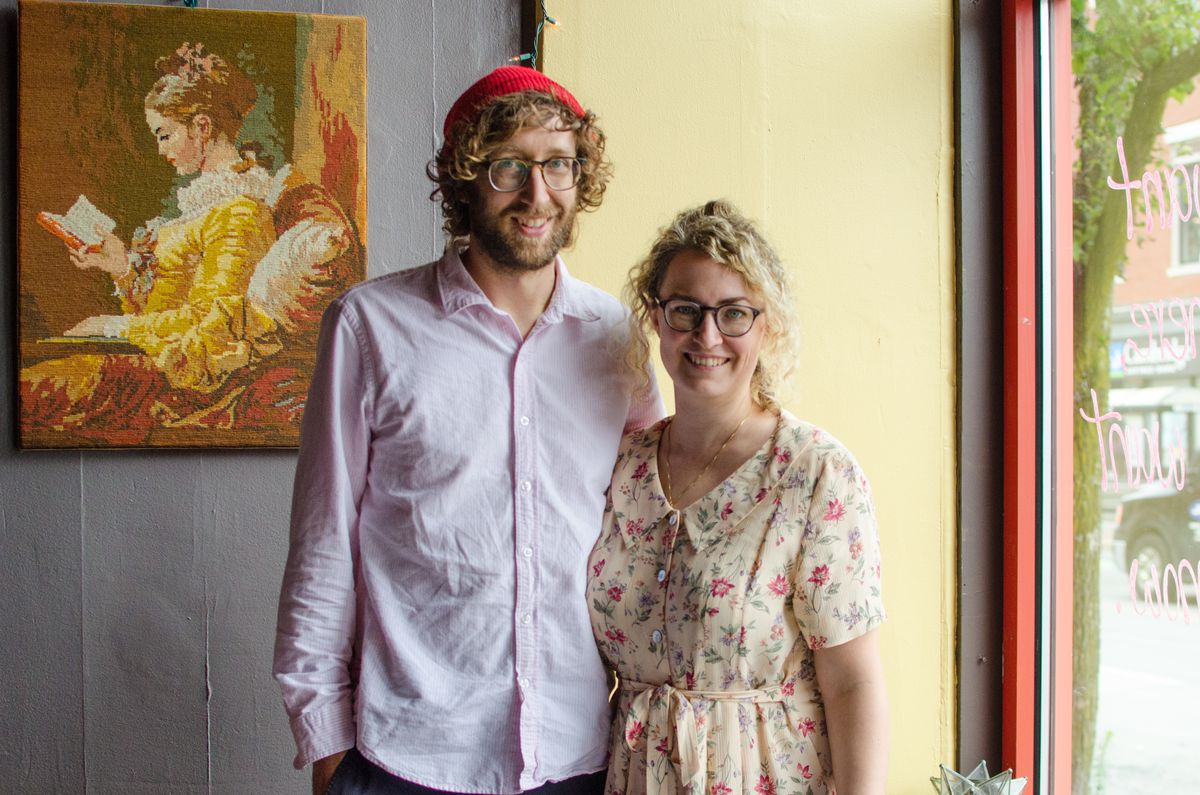 A man and woman stand next to each other against a wall (the left half is light gray, and the right half, leading to a sunlit window, is pale yellow.) Each wears glasses and has curly hair. The man wears a pale pink button-down shirt and a red beanie; the woman wears a floral dress.