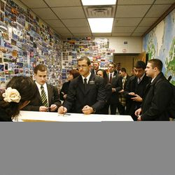 At left, Nivea Wright helps missionaries check out of the MTC. The wall at left is covered with postcards from around the world and at right is a world map at the Provo Missionary Training Center of The Church of Jesus Christ of Latter-day Saints in Provo, Utah Tuesday, Feb. 15, 2011.