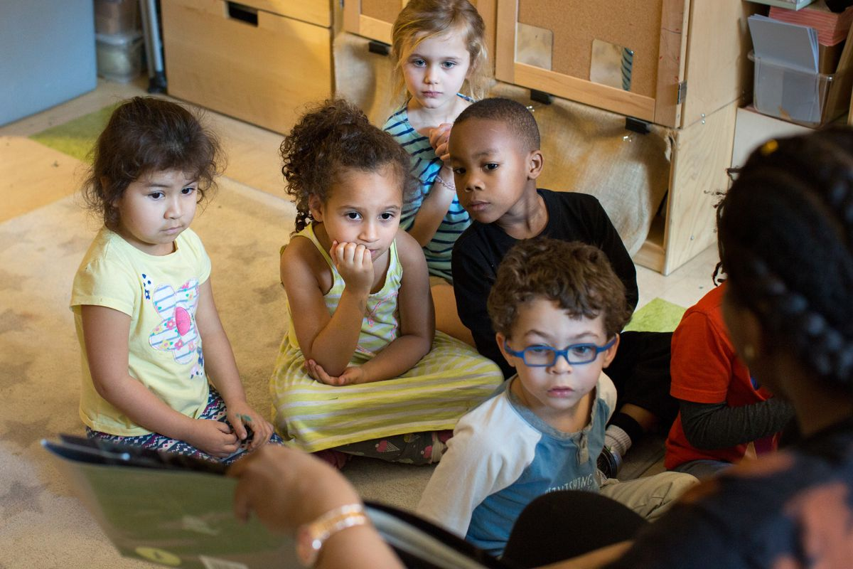 Six little children sit attentively on a rug in a classroom, looking at a book an adult facing them is showing.