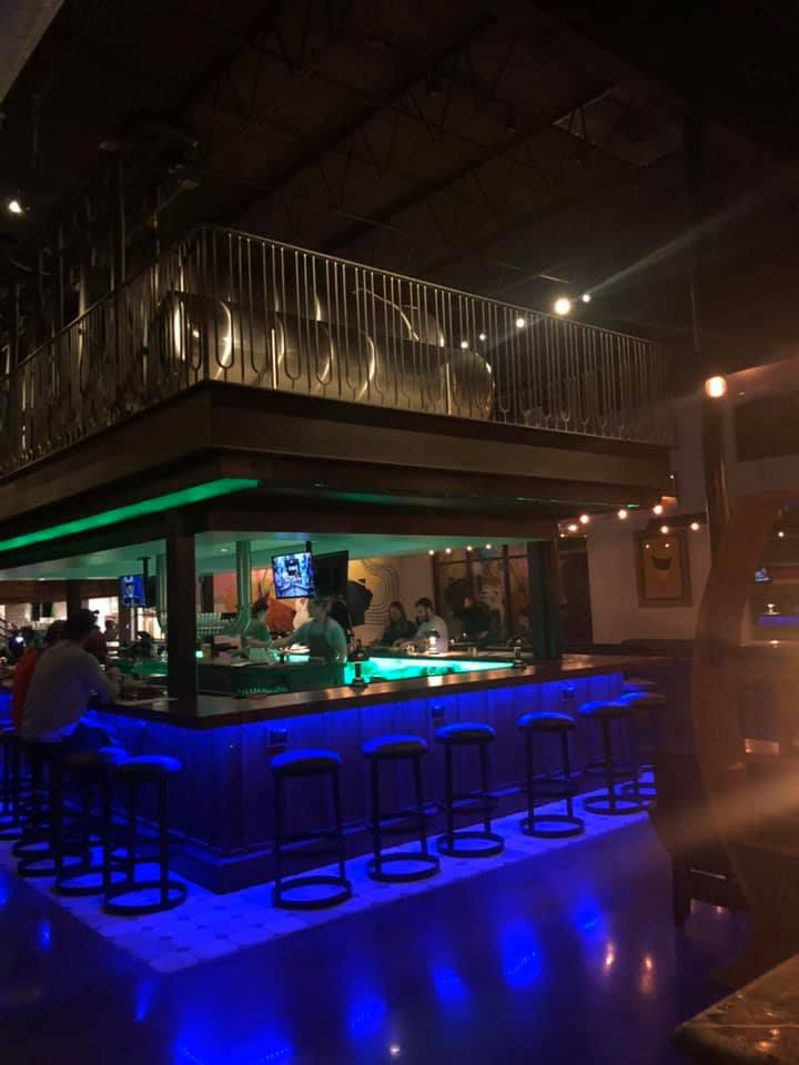 A shot of the U-shaped bar lit up at night with purple under lights and the mezzanine level above it