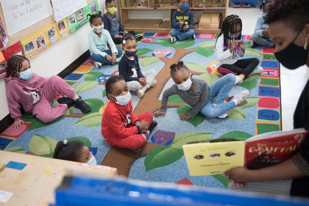 Preschool-age children sit on a colorful rug on the floor as a teacher in a mask reads to them from a yellow and red book.