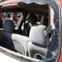 Iraqis inspect the scene of a car bomb attack in Baghdad, Iraq, Sunday, Sept. 30, 2012. A rapid-fire series of explosions in Baghdad while Iraqis were going to work on Sunday morning, killed and wounded scores of people, police said.