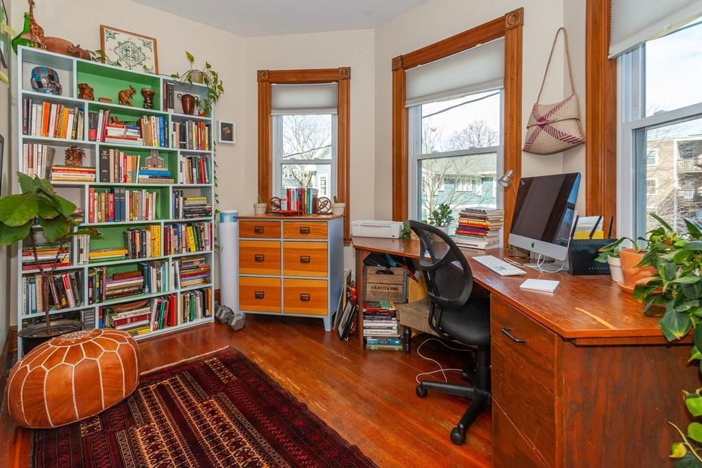 A home office in a bay-windowed area with shelves and a desk and chair.
